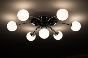 Fancy light fixture with round bulbs hanging from the ceiling.